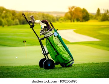 Golf niblick and putter in green bag and white ball on the field - luxury recreation for the high society