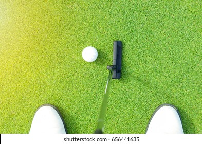 Golf player aim putter at golf ball, flare light effect on Left side, top view from golfer.
