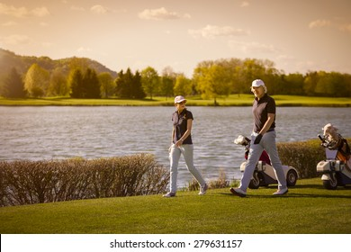 Golf player couple walking on fairway with beautiful lake in background at sunset.
