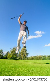 Golf player jubilating after a successful putt with a high jump into the air
