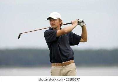 A golf player strikes a good shot