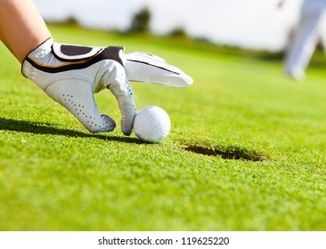 Golf player woman pushing golf ball into the hole
