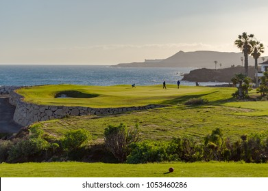 Golf players on a green facing the Atlantic Ocean on the island of Tenerife in Spain