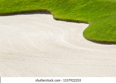 Golf Sand Trap or Bunker with Green Grass and Shallow Depth of Field Background.  Lots of Copy Space