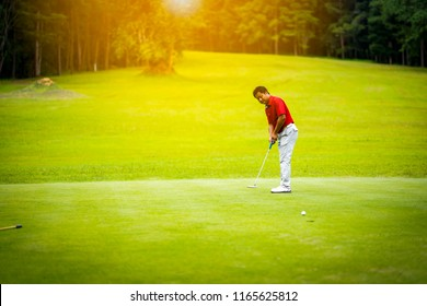 Golf sport concept, golfer putting ball to hole in open tournament of daytime of vacation on hills. Beautiful golf course on fairway and layout on forest blurred background