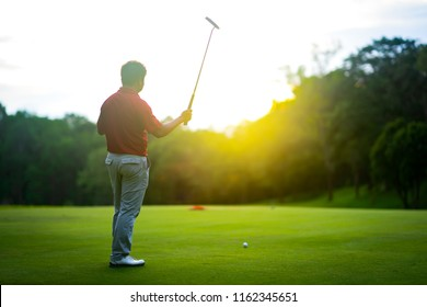 Golf sport concept, golfer raise golf club up show the winner of tournament in beautiful golf course on sunset. Light of sun beauty pass tree and player. Blurred background of ball and flag on green