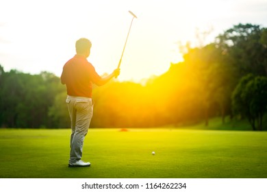 Golf sport concept, golfer raise golf club up show the winner of tournament in beautiful golf course on sunset on mountain and blurred tree forest