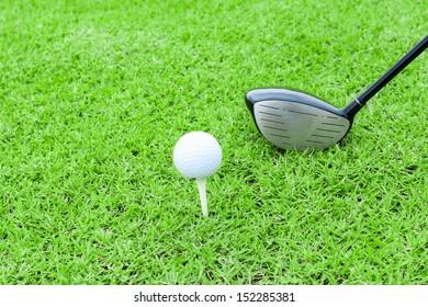 golf tee ball club driver in green grass course preparing to shot