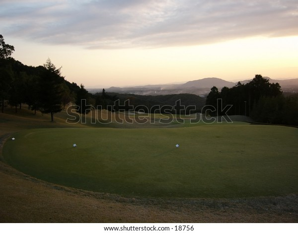 Golf tee at the top of a hill.