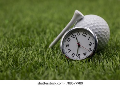 Golf time with golf ball and clock on green grass