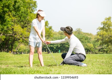 Golf trainer is training a new golf player