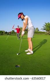 golf woman player green putting hole golf ball a man holding flag