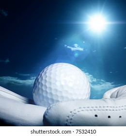golfball on a glove with a bright sun in the background