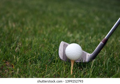 Golfball on a tee and club ready to strike make a golfing background
