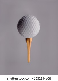 golfball on top of golden golf tee, grey background
