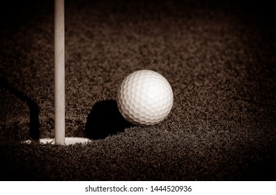 Golfball at the Rim of cup