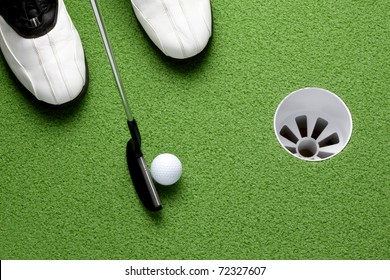 Golfer about to putt ball into cup on green