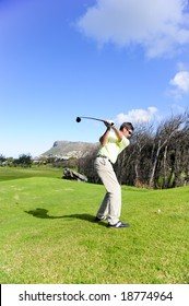 A golfer in action on a practice range, hitting the ball with a club.