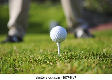 A golfer in action on a practice range. Focus on the ball and tee, with golfers legs faded out in the background.