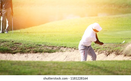 Golfer action trying to hit the ball out from sand bunker. Selective focus