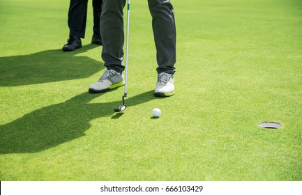 Golfer aim putting golf ball to hole