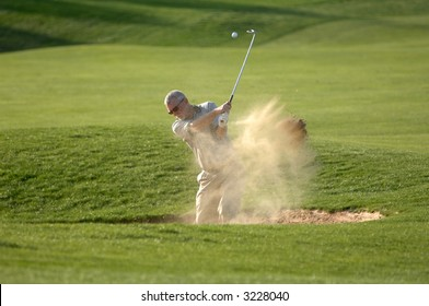a golfer blasts out of a sand trap