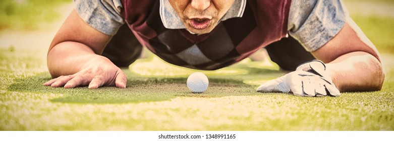 Golfer blowing ball in the hole on the golf course