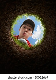 golfer blowing golf ball, view from inside the hole