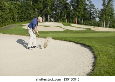 Golfer in a blue shirt blasting out of bunker onto green