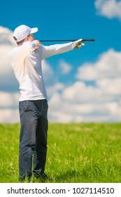 Golfer in cap with golf club in field posing