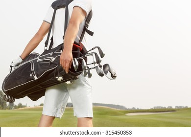Golfer carrying his golf bag across a golf course