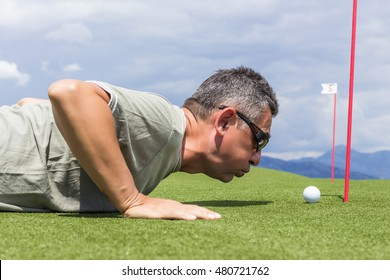 Golfer cheating by blowing the ball into the hole