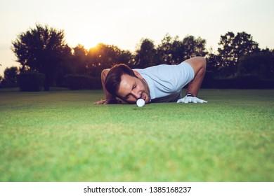 Golfer checking line of putt on green