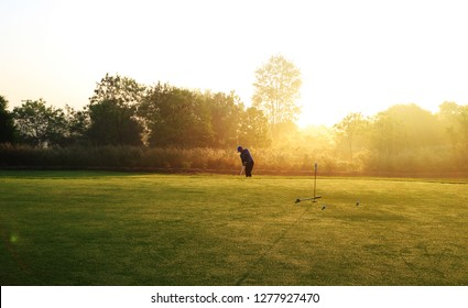Golfer is chipping golf ball on the green for practice , morning time