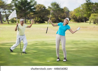 Golfer couple celebrating success while standing on field