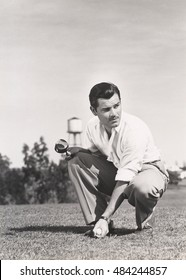 Golfer crouching on golf course