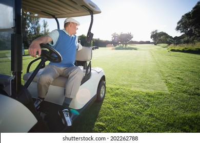 Golfer driving his golf buggy in reverse on a sunny day at the golf course