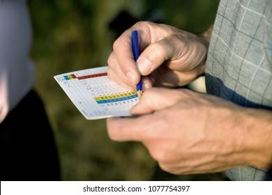 Golfer filling in a score card