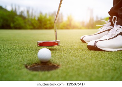 Golfer focus putting golf ball into the hole during sunset,Healthy and Lifestyle Concept