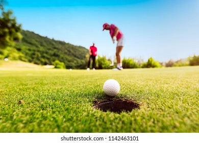 Golfer focus putting golf ball into the hole during sunset,Healthy and Lifestyle Concept.