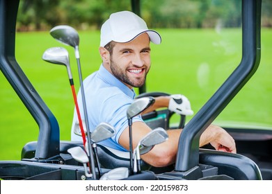 Golfer in golf cart. Rear view of young happy male golfer driving a golf cart and looking over shoulder