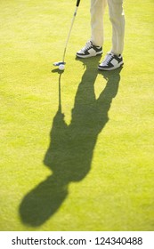 Golfer with golf club and ball standing on green grass, leg view and shadow silhouette of golpher on grass