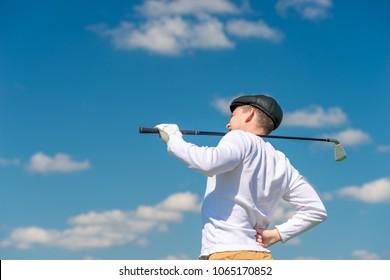 Golfer with a golf club rubs a sick back on the field