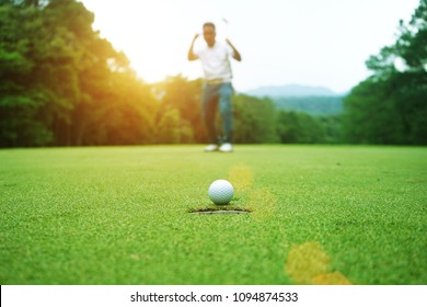 golfer happy for successful putt on the green, on sun set evening time.
