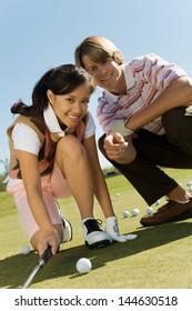 Golfer helping teenage girl line up shot