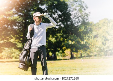 Golfer his carrying golf bag on the golf course.