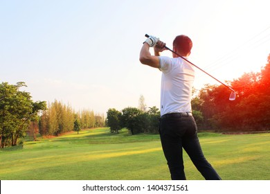 The golfer hit the ball in full swing to compete in the green lawn in the sunshine.