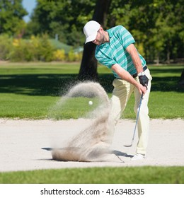 Golfer hits the ball out of sand trap. Focus on golfer, ball and sand wave in motion blur.
