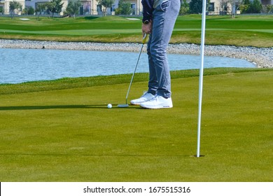 a Golfer hits the ball slowly to the hole.
