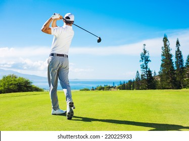 Golfer Hitting Ball with Club on Beatuiful Golf Course